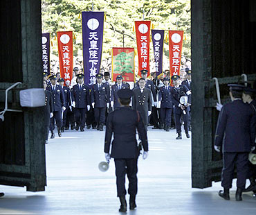 Well-wishers holding flags reading 'Banzai Emperor' or 'Long Live His Majesty the Emperor' are led by Imperial Guard police officers during a public appearance by Emperor Akihito and members of the imperial family for New Year celebrations at the Imperial Palace in Tokyo
