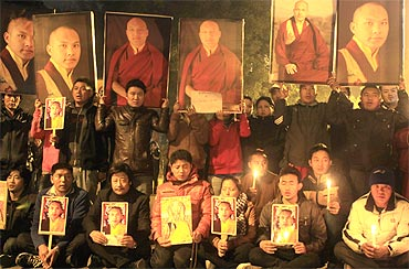 Tibetan exiles hold portraits of the Karmapa Lama during a candlelight vigil in New Delhi
