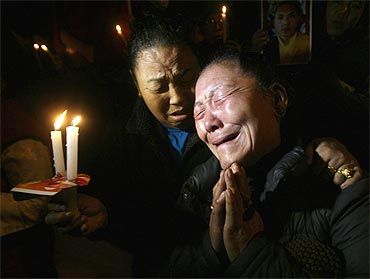 Tibetan exiles weep during a candlelight vigil in support of the Karmapa Lama in New Delhi