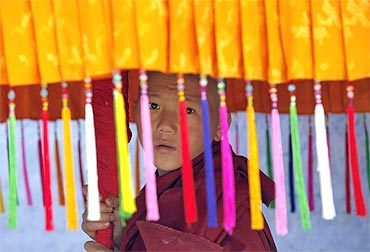 A young monk holds a traditional parasol as he waits for the arrival of Dalai Lama in Pemayangtse monastery in Sikkim
