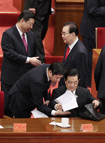 Hu Jintao (bottom R), China's president and general secretary of the Communist Party of China (CPC), gathers his papers as Vice President Xi Jingping (L) shakes hands with former Premier Li Peng after the celebration of the 90th anniversary.