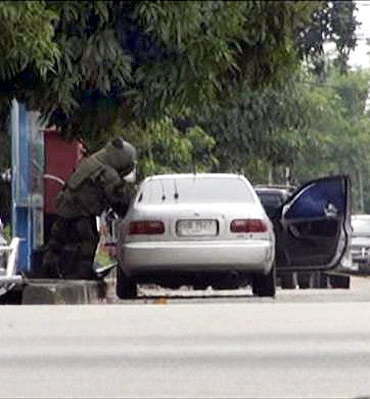 A member of a Thai bomb squad checks a car in Narathiwat province, south of Bangkok