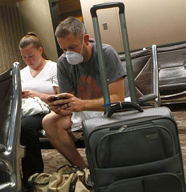 Jason Wallace wears a face mask and plays with his phone as he sits with his wife Emily Wallace inside Sky Harbor International Airport during the storm