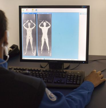 A TSA officer demonstrates what the images form the Advanced Imaging Technology unit look like at John F Kennedy International Airport's Terminal 8 passenger security checkpoint