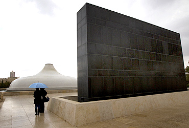 People stand under an umbrella in front of the Shrine of the Book, which houses the Dead Sea Scrolls and other ancient manuscripts, at the Israel Museum in Jerusalem.