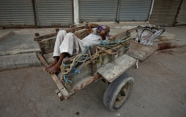 A man rests on a donkey cart in front of closed shops in Karachi