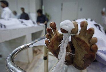 Men stand next to the body of a man who was killed by unidentified gunmen, last night at a morgue in Karachi