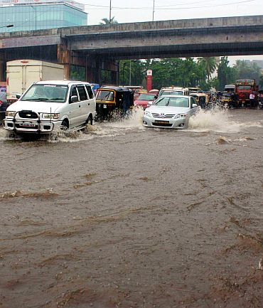 Vehicles cross a flooded intersection in Andheri