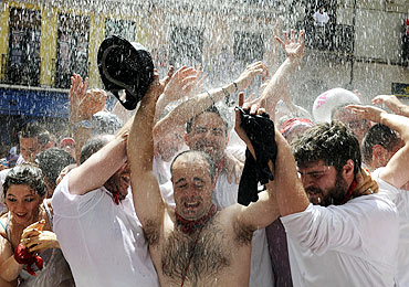 Revellers are showered with water during the start of the San Fermin Festival