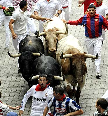 Runners sprint in front of Torrestrella fighting bulls
