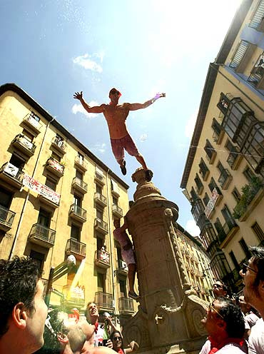 A reveller jumps from a fountain at the Plaza de Navarreria
