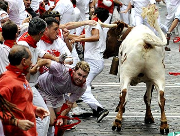 A steer pushes a reveller with his horn during the first bull run