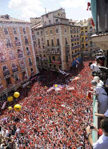 Revellers hold up red scarves during the start of the San Fermin Festival