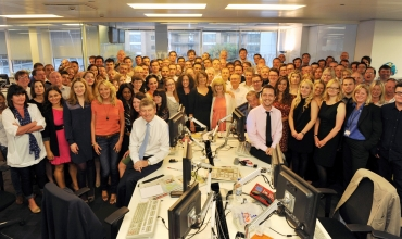 The News Of The World editor, Colin Myler, poses for a photograph with the staff of the newspaper in their newsroom in London
