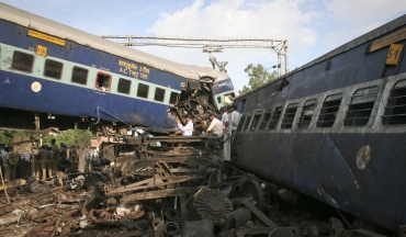 People search through the mangled carriages of Kalka Mail