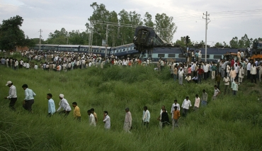 People walk through the grass near the mangled carriages of Kalka Mail which derailed near Fatehpur