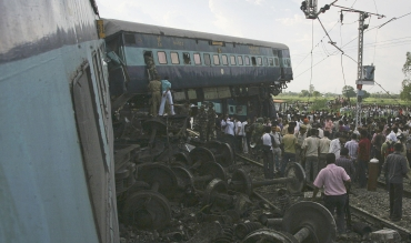 People watch as rescue personnel search for survivors in the mangled carriages of Kalka Mail