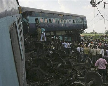 People watch as rescue personnel search the mangled carriages of the Kalka Mail train which derailed near Fatehpur