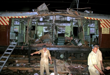 Workers stand near a local train damaged by the serial blasts in Mumbai