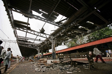People walk on a damaged railway platform hit by one of the blasts