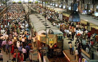 Commuters stand still at a crowded railway station to pay homage during a two-minute long remembrance for bomb blast victims in Mumbai