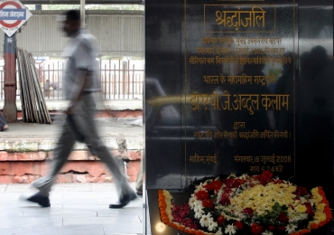 A man walks past a memorial which was erected as a tribute to blast victims at a railway station