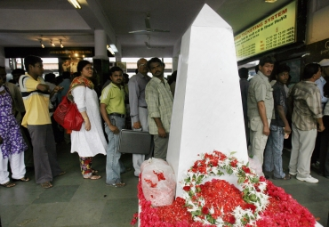 Commuters stand in a queue to purchase train tickets next to a memorial for train blast victims