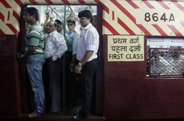 Train commuters travel in the refurbished coach 864A that was damaged in one of the bomb blasts