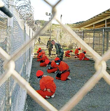 Detainees sit in a holding area during their processing into the temporary detention facility at Camp X-Ray inside Guantanamo Bay