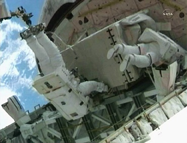 Astronaut Ron Garan (C),holds the pump module as he is assisted by fellow spacewalker Mike Fossum (R) as the pair secure the module in Atlantis' payload bay for its return to Earth in this still image taken from NASA TV