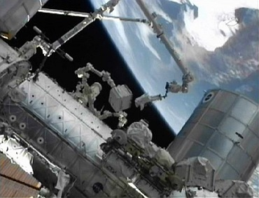 Mike Fossum (C), on the end of the International Space Station's Canadarm2 works outside the station during his spacewalk in this image from NASA TV