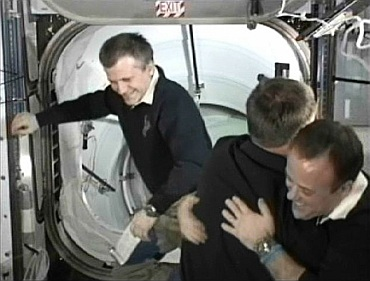Space shuttle Atlantis Commander Chris Ferguson and station flight engineer Ron Garan hug as International Space Station Commander Andrey Borisenko floats in the background after docking and hatch opening between the two spacecraft in this image from NASA TV