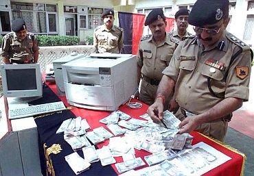 Police testing the authenticity of currency notes seized in a raid