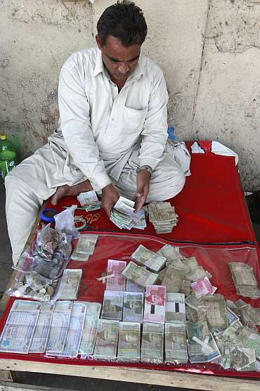 A currency dealer counts Pakistani rupees at his roadside shop in Karachi