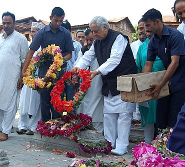 Senior PDP leader Mufti Mohammed Sayeed offers floral tributes on the martyr's graveyard in Srinagar