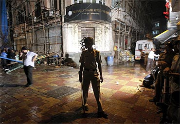 A policeman stands guard at the site of an explosion in Zaveri Bazaar blast site in Mumbai