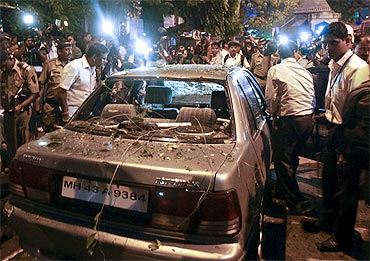 Plainclothed policemen surround a vehicle which was damaged at the site of an explosion in Dadar