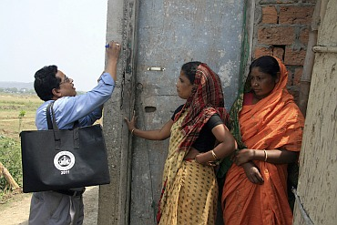 A census official (L) marks a house after collecting details from a village resident