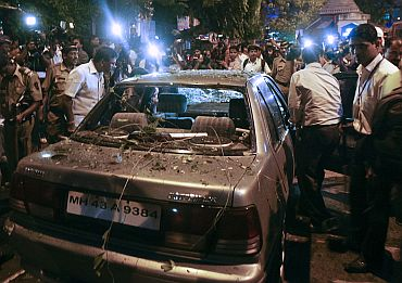 Policemen surround a vehicle which was damaged at the site of an explosion in the Dadar