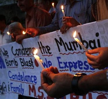 People hold candles during a prayer ceremony for the victims of Wednesday's triple explosions in Mumbai