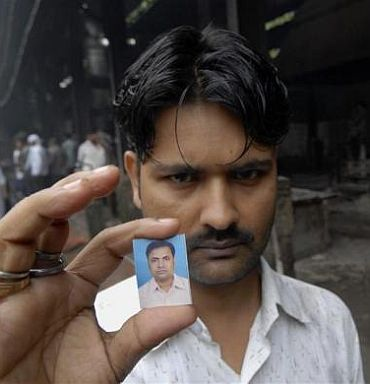 Mahant Mandal displays a passport photograph of his brother Kishan, who was killed in one of the three blasts that took place on Wednesday