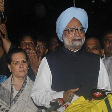 Prime Minister Manmohan Singh speaks to the media as Congress party chief Sonia Gandhi watches after they met the victims of Wednesday's triple explosions at a hospital in Mumbai