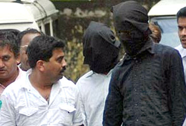 Police leading away two suspected Indian Mujahideen suspects in Mumbai on July 12