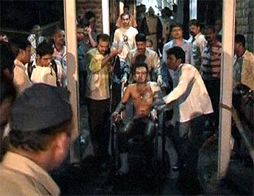 A victim is taken away on a wheelchair at a blast site