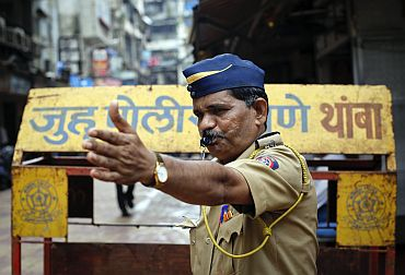 A policeman whistles and gestures to onlookers at Zaveri Bazaar in Mumbai