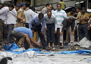 A man moves debris from the blast site at Zaveri Bazaar in Mumbai