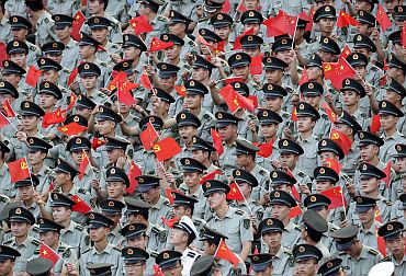 Soldiers wave Chinese flag during CPC's anniversary celebrations in Chongqing municipality