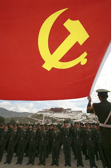 Policemen review the oath that they took when they joined the CPC in front of Potala Palace in Lhasa