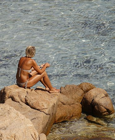 A woman sits by the rocks at the Ramizzo beach in the so called 'Emerald Coast' of the Sardinia island in Italy