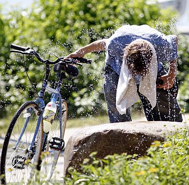 Biker Jordan Richardson seeks relief from high temperatures near Lake Calhoun in Minneapolis, US. A heat wave with oppressive temperatures and stifling humidity lingered and intensified in the midsection of the country and was expected to expand eastward as the week continued